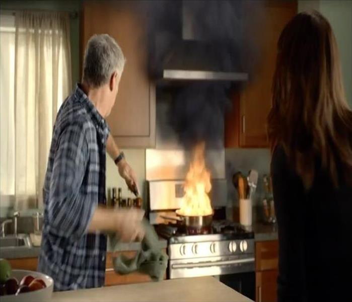 husband and wife looking at a fire in frying pan on stove